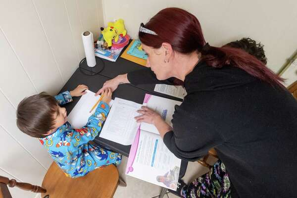 Jacoby Crisp, 6, gets instruction from his mom on his kindergarten work at their home. Amber Feener has three kids in Port Necehs-Groves schools and homeschooling during the Covid-19 pandemic began for all of them on Wednesday, March 25, 2020. Fran Ruchalski/The Enterprise