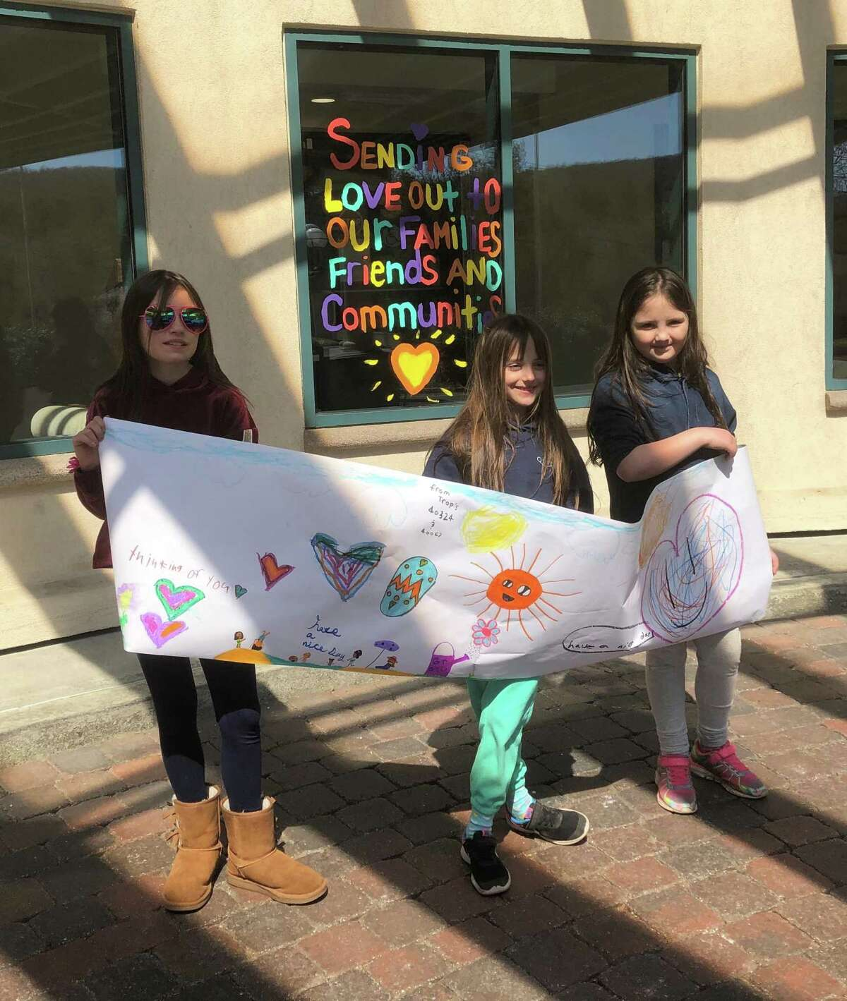 Members of Girl Scout Troop 40324 and Brownie Troop 40067 in New Milford, from left to right,Lydia, Sonya and Alys Hyde, recently paid a visit to Candlewood Valley Health & Rehabilitation Center in town to deliver a message of cheer.