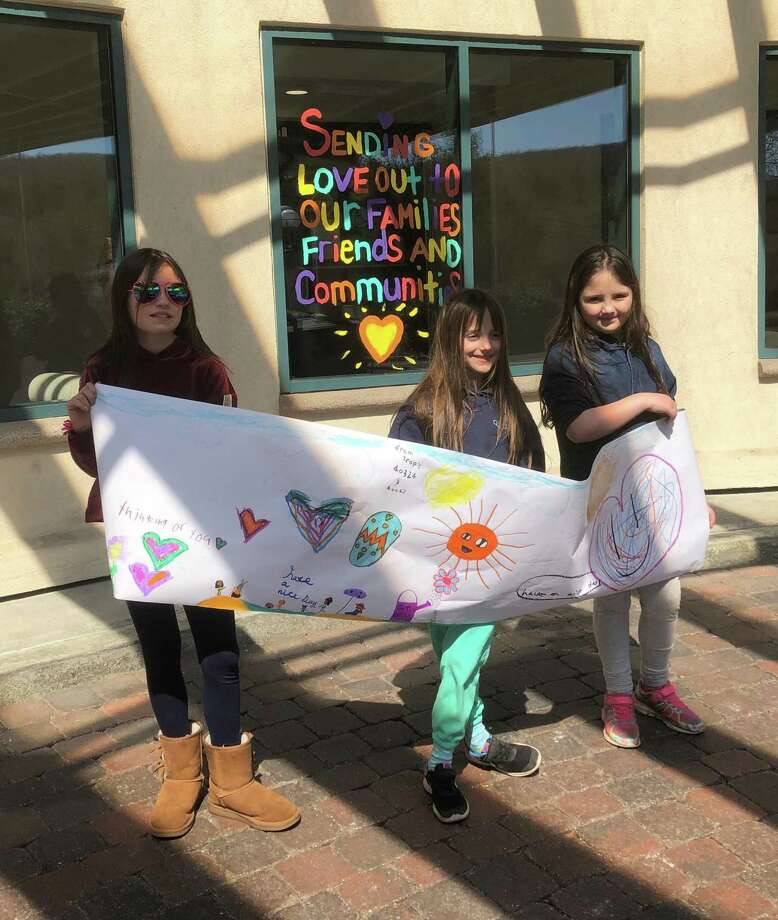 Members of Girl Scout Troop 40324 and Brownie Troop 40067 in New Milford, from left to right,Lydia, Sonya and Alys Hyde, recently paid a visit to Candlewood Valley Health & Rehabilitation Center in town to deliver a message of cheer. Photo: Courtesy Of Carolyn Hyde