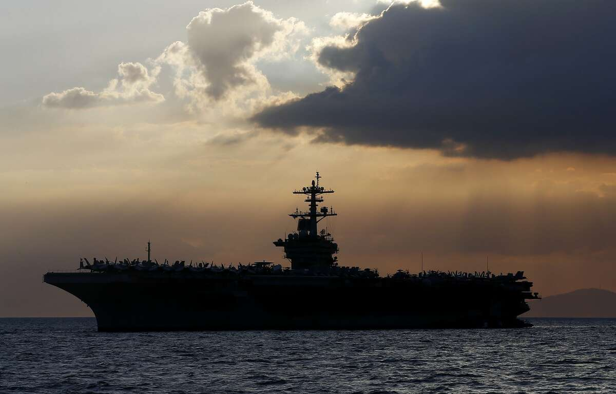 FILE - In this April 13, 2018, file photo the USS Theodore Roosevelt aircraft carrier is anchored off Manila Bay west of Manila, Philippines. The captain of the U.S. Navy aircraft carrier facing a growing outbreak of the coronavirus is asking for permission to isolate the bulk of his roughly 5,000 crew members on shore, which would take the warship out of duty in an effort to save lives. The ship is docked in Guam (AP Photo/Bullit Marquez, File)