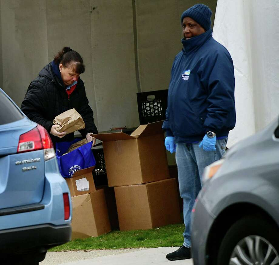 Volunteers hand out food to parents at Tracey Elementary School Tuesday, March 31, 2020,in Norwalk, Conn. Photo: Erik Trautmann / Hearst Connecticut Media / Norwalk Hour