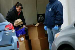 Volunteers hand out food to parents at Tracey Elementary School Tuesday, March 31, 2020,in Norwalk, Conn.
