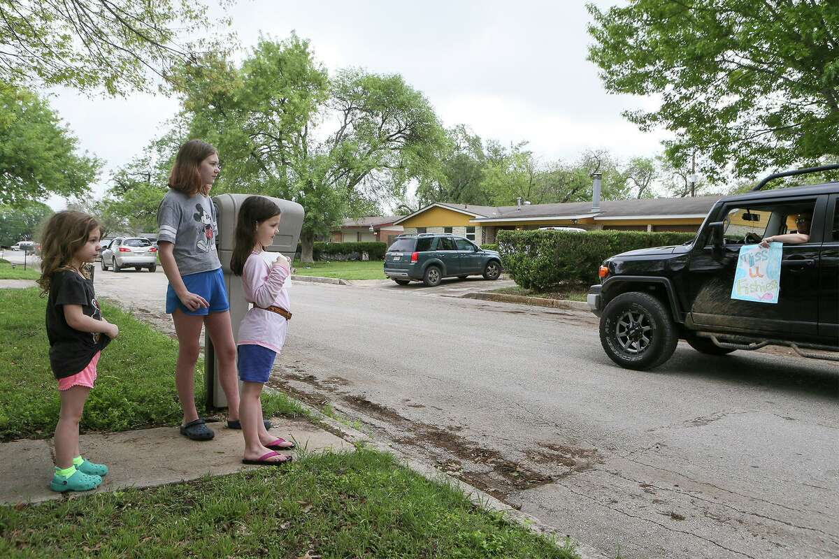 Siblings (from left) Rose Baker, 4, sixth-grader Haylie Doty, 12, and kindergartner Quinn Baker, 6, greet a caravan of teachers from Rose Garden Elementary on a teacher