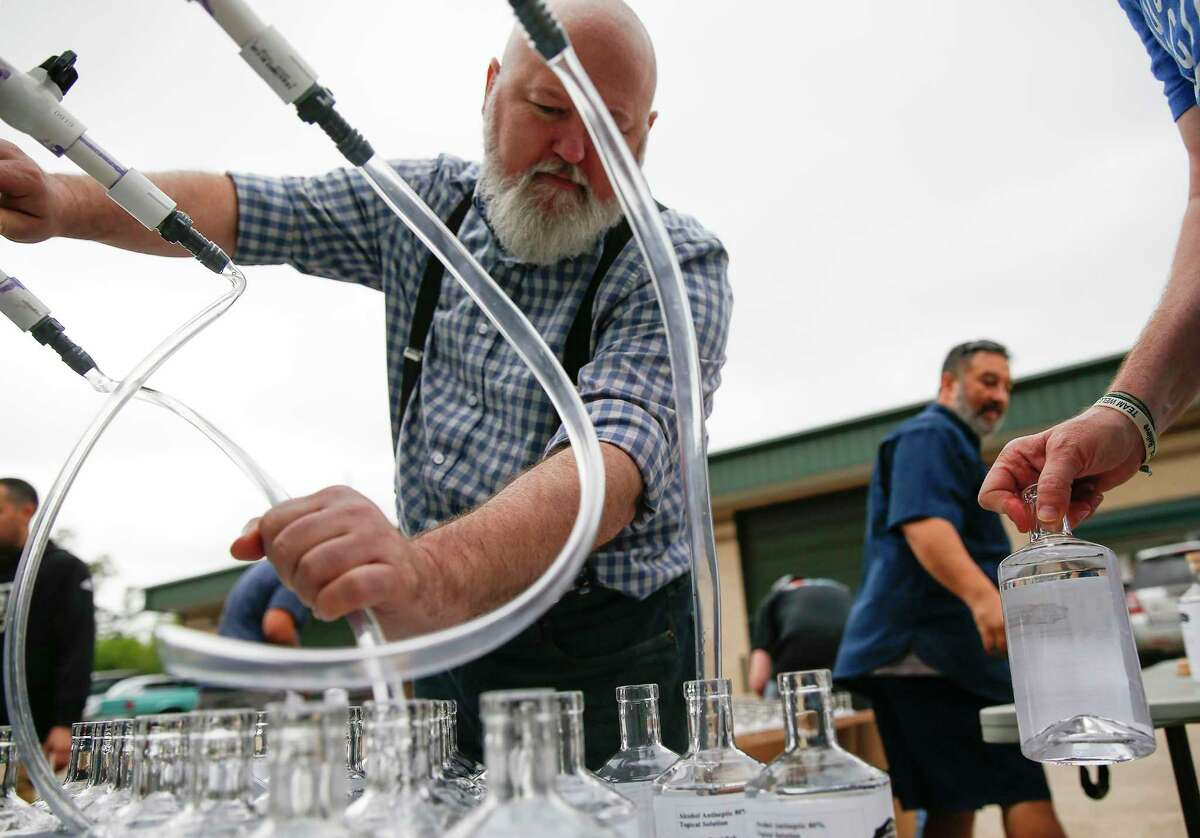 Joe Amato pours hand sanitizer at Whitmeyer's Distillery to distribute for free out of their Houston location on Tuesday, March 31, 2020. The distillery ran out of hand pumps so decided to use their whiskey bottles.