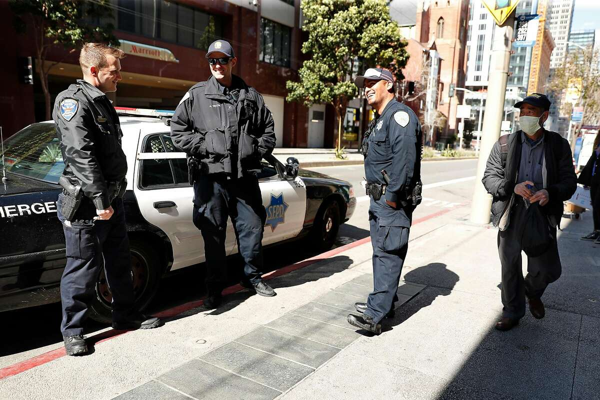 San Francisco Police officers Tyler Cope, Andre Taylor and Lazar Villalozano chat on Mission Street at 4th Street in San Francisco, Calif., on Thursday, March 26, 2020.