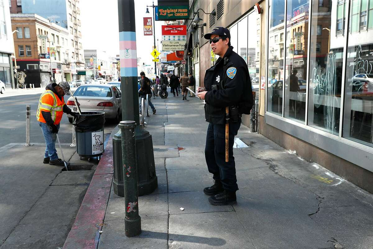 San Francisco Police officer Sam Fung walks his beat on 6th Street at Market Street in San Francisco, Calif., on Thursday, March 26, 2020.