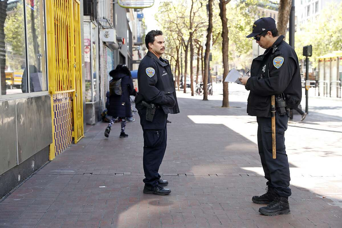 San Francisco Police officers Sam Fung (right) and James Puccinelli stand at 6th and Market Streets in San Francisco, Calif., on Thursday, March 26, 2020.