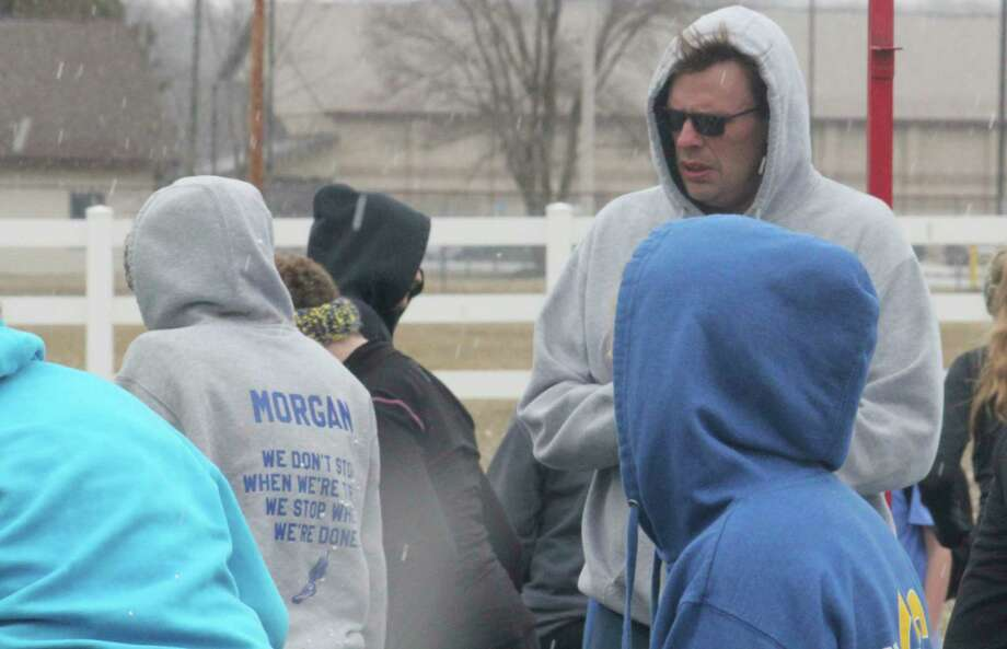 Evart track coach Todd Scott (right) talks to his team during the 2018 preseason when March weatherwas very wintry. (File photo)