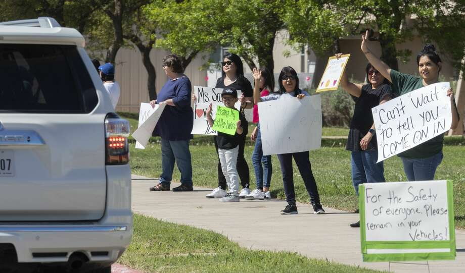 Staff from Helen L. Greathouse Children's Center, Manor Park Community Children's Center and Pre-K Academy at Midland College hold signs as parents drive their students past teachers and staff 03/31/2020 around the parking lot at Midland College. Tim Fischer/Reporter-Telegram Photo: Tim Fischer/Midland Reporter-Telegram