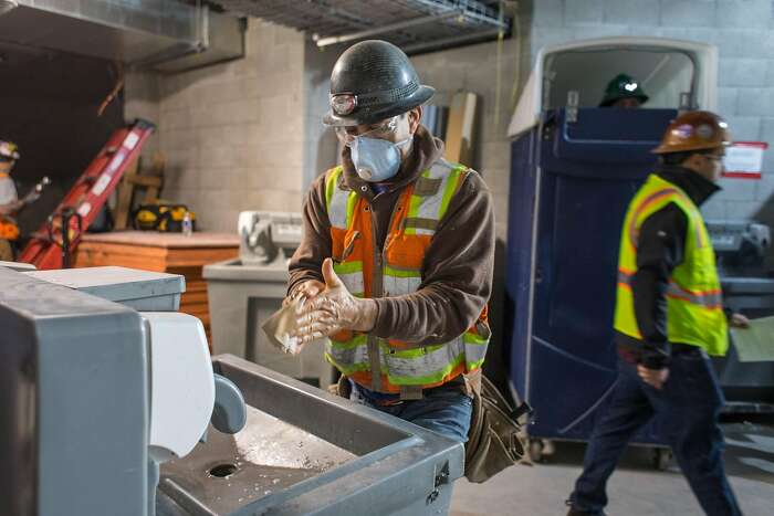 Jesus Camacho washes his hands at a cleaning station on a construction site for a new housing project at 950 Gough Street on Tuesday, March 31, 2020 in San Francisco, Calif.