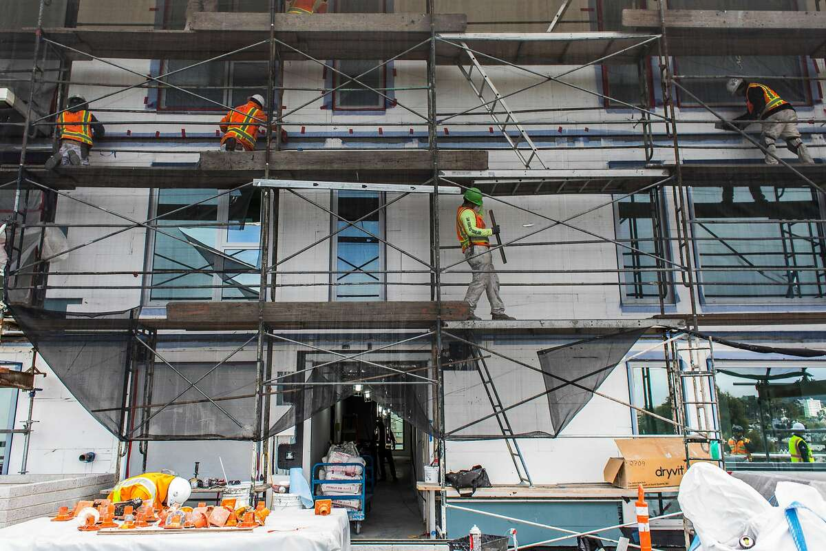 Construction workers work on a new housing project at 950 Gough Street on Tuesday, March 31, 2020 in San Francisco, Calif.
