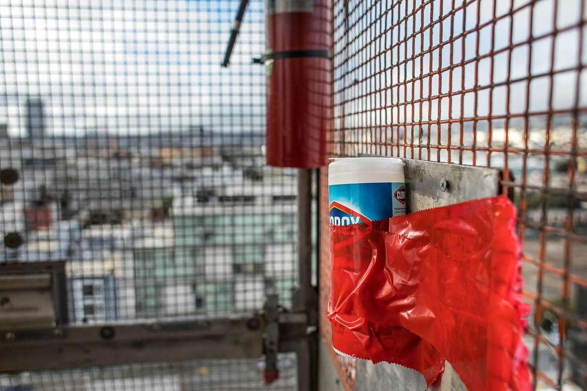 A bottle of sanitizing wipes is taped to the side of a construction lift in a new housing project at 950 Gough Street on Tuesday, March 31, 2020 in San Francisco, Calif.