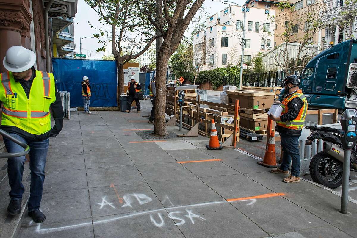 Lines on the street mark spots where workers can stand six feet apart before entering a new housing project at 950 Gough Street on Tuesday, March 31, 2020 in San Francisco, Calif.