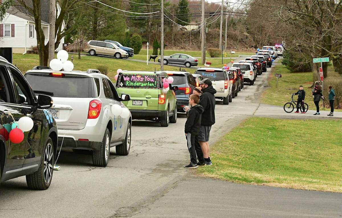 People on Orchard Lane wave to teachers and staff from Gardner-Dickinson School as they ride in a Royal Parade in their cars on Tuesday, March 31, 2020 in Troy, N.Y. The staff were waving to families who have to stay at home because of the Coronavirus pandemic. (Lori Van Buren/Times Union)