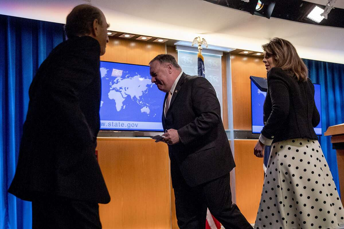 Special Representative for Venezuela Elliott Abrams, left, takes the podium as Secretary of State Mike Pompeo, accompanied by State Department spokeswoman Morgan Ortagus, right, departs after speaking at a news conference, Tuesday, March 31, 2020, in Washington. (AP Photo/Andrew Harnik, Pool)