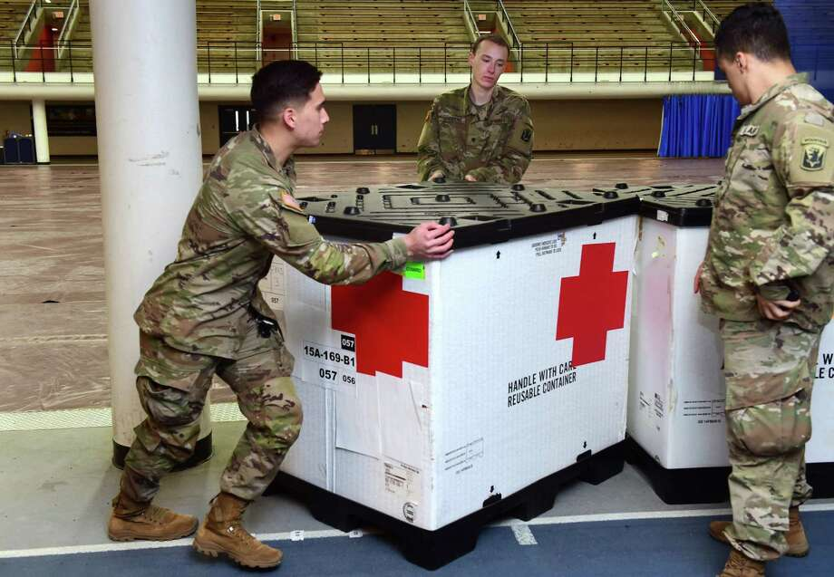 Members of the Connecticut National Guard move boxes of supplies into place in Southern Connecticut State University's Moore Field House in New Haven in preparation for a 250-bed field hospital on March 31, 2020. Photo: Arnold Gold / Hearst Connecticut Media / New Haven Register