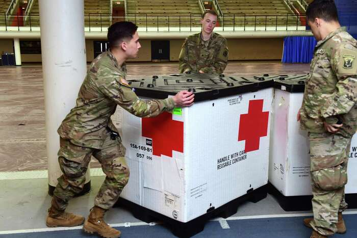 Members of the Connecticut National Guard move boxes of supplies into place in Southern Connecticut State University's Moore Field House in New Haven in preparation for a 250-bed field hospital on March 31, 2020.