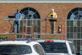 Pastor Mark Carpenter speaks to his congregation from a scaffold accompanied by Daniel Hawk on the keyboard as worshippers at First Baptist Church in Silsbee held their weekly service in the church parking lot with the audio broadcast on a local radio frequency on Sunday, March 29, 2020. Fran Ruchalski/The Enterprise
