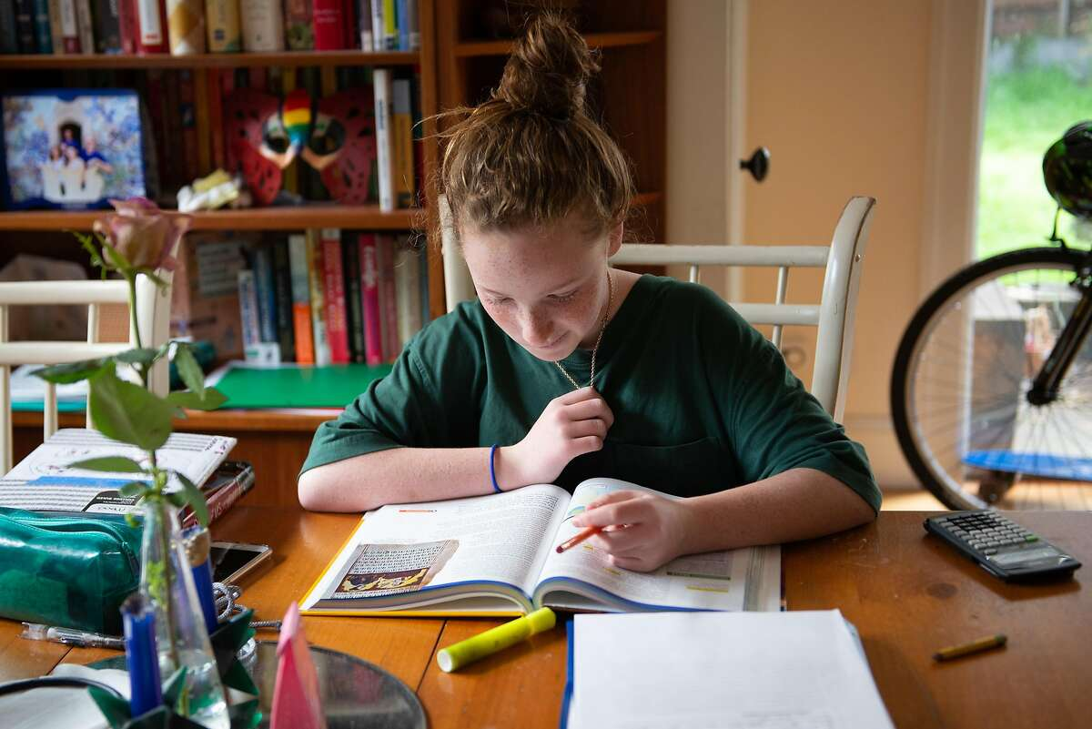 Juliet Schoenberger, (11), a 6th grader at Claremont Middle School does school work while she and her family self isolate during the shelter-in-place order on March 20,2020 in Oakland, Calif.
