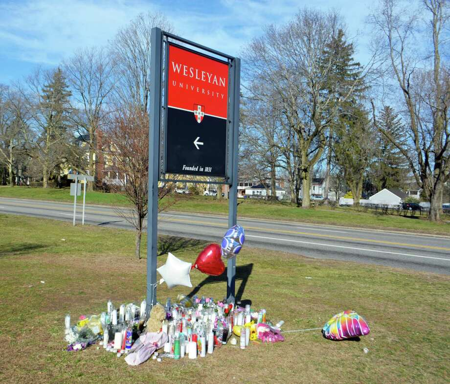 Candles are shown the Wesleyan University sign at the corner of High Street and Washington Street in Middletown. The memorial is meant to honor the life of Brooke Rich, a Middletown mother and Wesleyan dining services worker who died March 4 following a hit-and-run crash. Photo: Hearst Connecticut Media File Photo