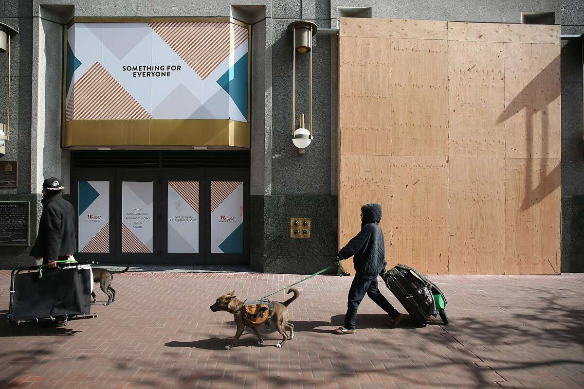 Pedestrians walk past a part of Westfield Mall that has been boarded up on Friday, March 27, 2020 in San Francisco, Calif.