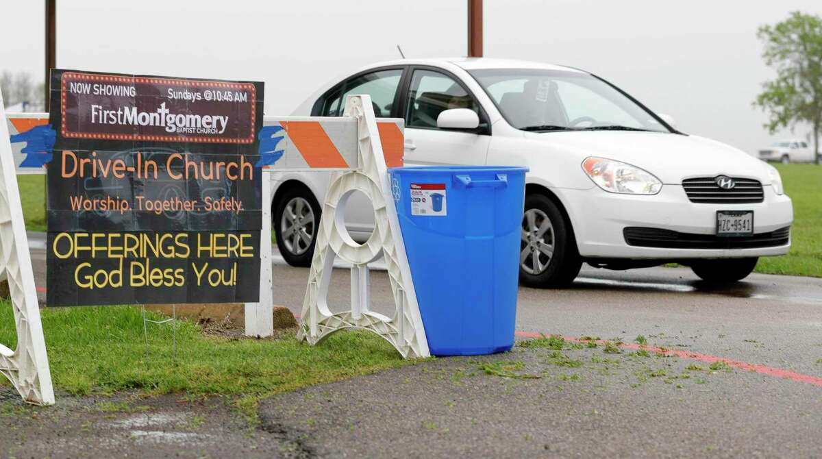 A car drive past a sign for a drive-in style service at First Montgomery Baptist Church is seen, Sunday, March 22, 2020, in Montgomery. More than 200 parishioners attended the service.