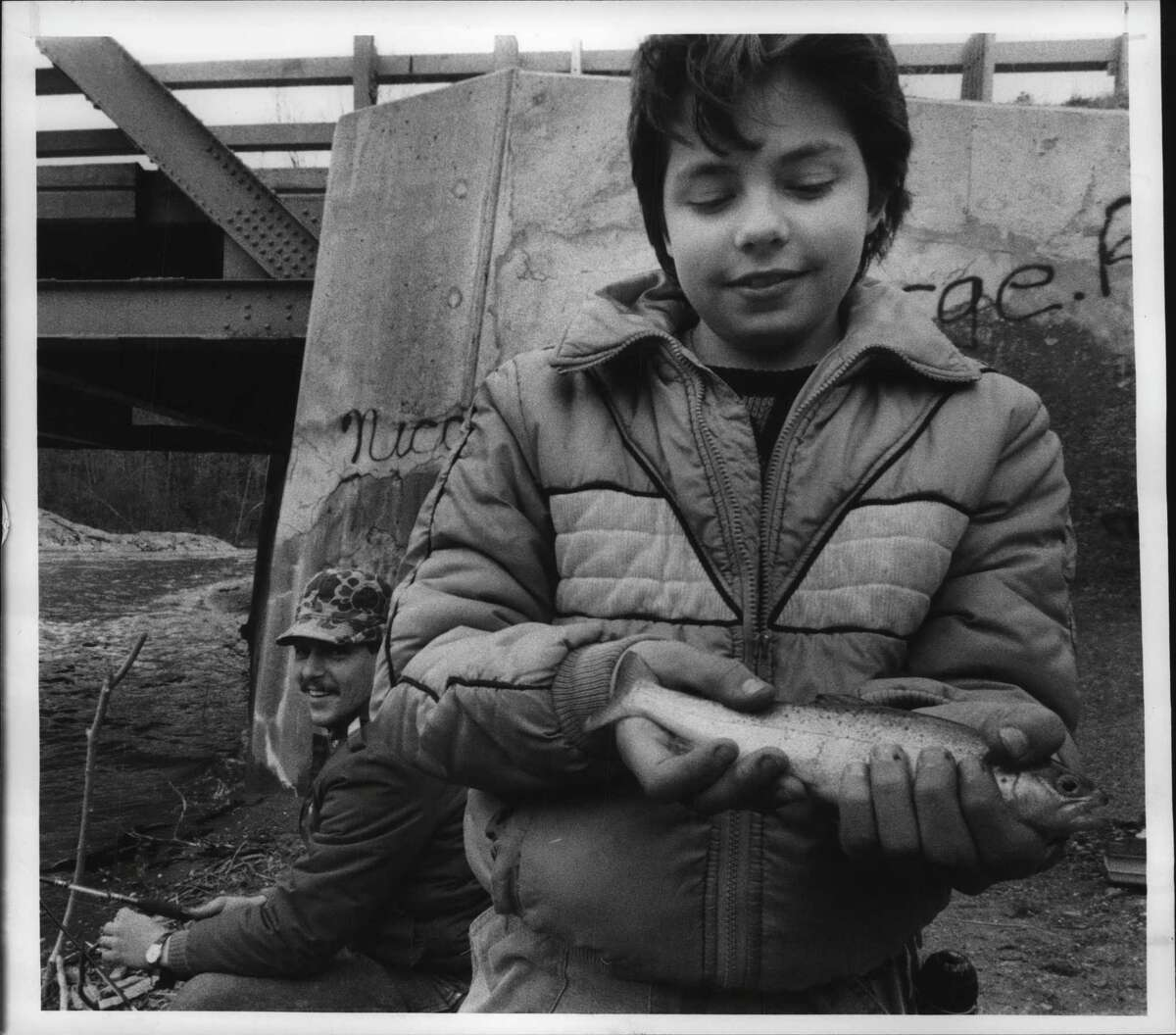 Route 66, east of the Village of Nassau, New York - Jason McBee, of Slingerlands, holds a keeper brown caught by his uncle Skie McBee, left, of Waterford, in the roily waters of the Kinderhook Creek. McBee took the trout on a heavily weighted worm. April 1, 1989 (John Carl D'Annibale/Times Union Archive)