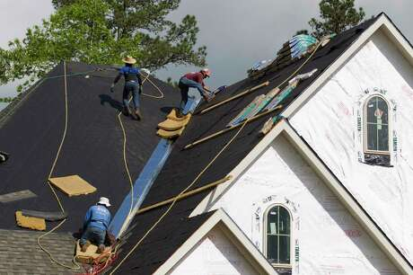 Workers install roofing material on a home in The Woodlands Hills, Montgomery County's newest a master-planned community near Willis, Thursday, April 11, 2019, in Willis.