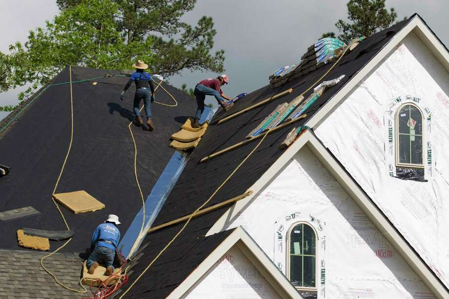 Workers install roofing material on a home in The Woodlands Hills, Montgomery County's newest a master-planned community near Willis, Thursday, April 11, 2019, in Willis. Photo: Jason Fochtman, Houston Chronicle / Staff Photographer / © 2019 Houston Chronicle