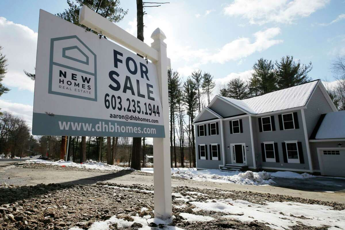 """FILE - In this Feb. 20, 2020 file photo, a """"For Sale"""" sign stands in front of a newly constructed home in Londonderry, N.H. U.S. home sales retreated 1.3% in January from the prior month, but low mortgage rates helped enable an increase in purchases from a year ago. Americans signed more contracts in February to buy homes, but the gains are likely relics of a moment before the coronavirus outbreak sent the U.S. economy spiraling into a likely recession. (AP Photo/Charles Krupa, File)"""
