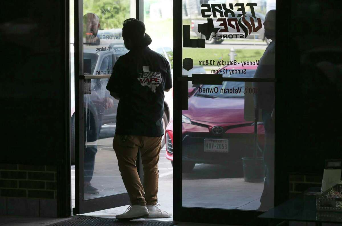 A customer waits outside the door of Texas Vape, which was ordered to close under the citywide ban on certain businesses. Owner Richard Tisdale disputes the city's interpretation of the ban.