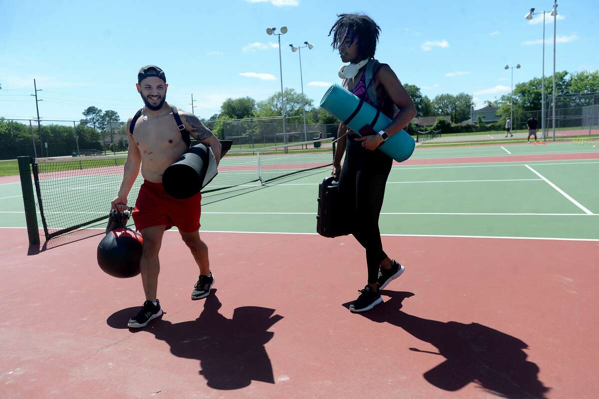 Chris Gutierrez jokes with Aarynn Davis after they finish a workout at Rogers Park Tuesday. The fitness enthusiasts who worked out together routinely at Exygon and 183 Hex, brought their equipment to maintain their usual routines outdoors on a bright day.