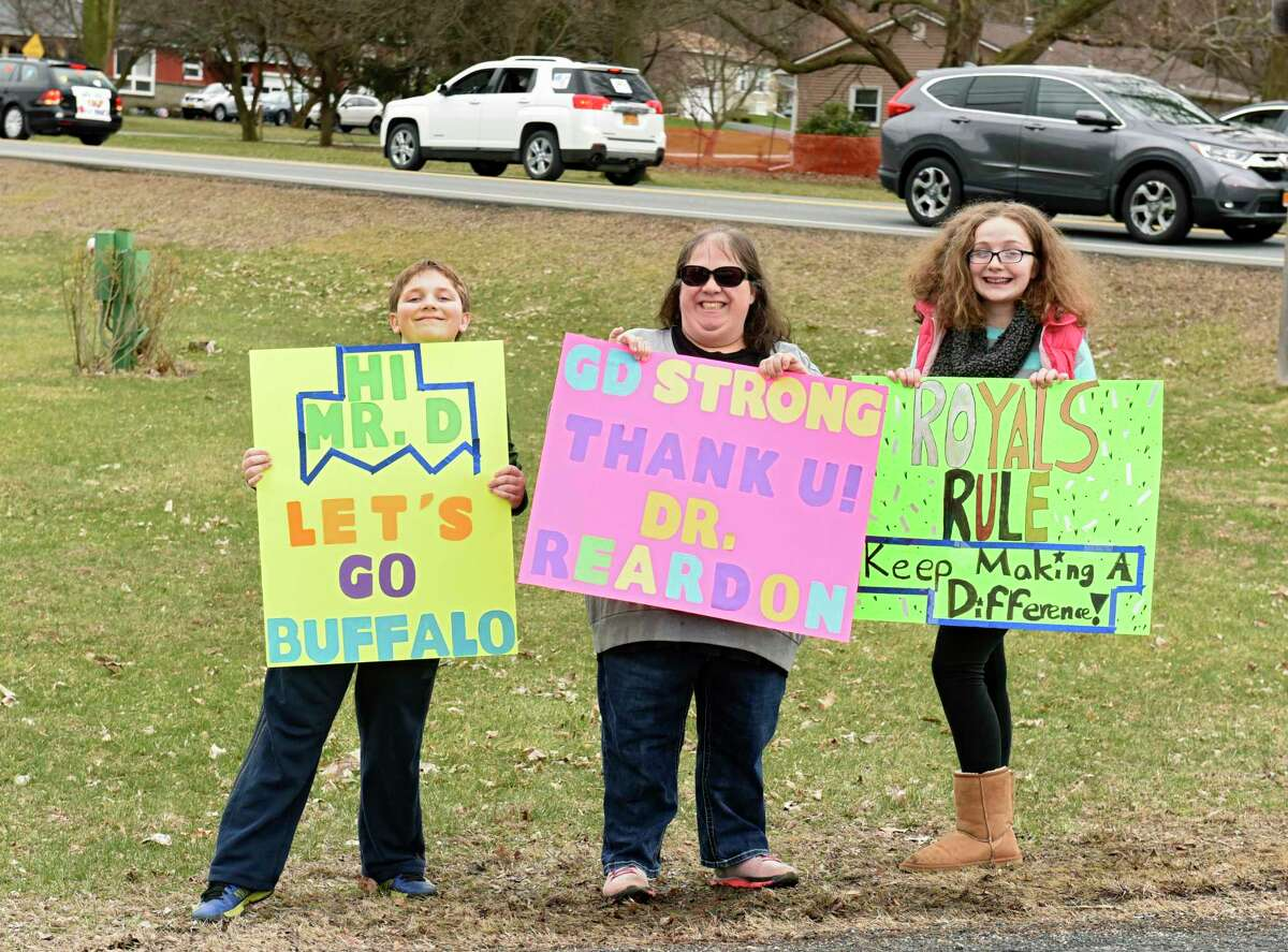Parents and students with signs wave to teachers and staff from Gardner-Dickinson School as they drive in a Royal Parade in their cars on Tuesday, March 31, 2020 in Troy, N.Y. The staff were waving to families who have to stay at home because of the Coronavirus pandemic. (Lori Van Buren/Times Union)