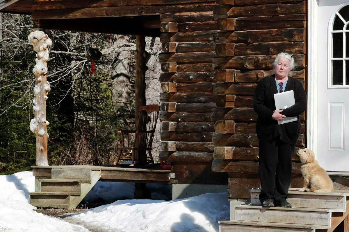 Julie Dolan, chair of her town's Broadband Committee, poses with her computer on the steps of her family's rural home in Sandwich, N.H., Thursday, March 26, 2020. In the town of 1,200 best known as the setting for the movie a€œOn Golden Pond,