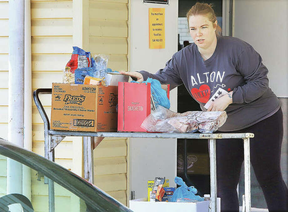 Tiffany Hilger, a volunteer at the Crisis Food Center in Alton, talks to clients waiting in their cars outside the food panty Tuesday. The Crisis Food Center has joined other local food pantries by shifting to a drive-through operation for the needy picking up food. Photo: John Badman | The Telegraph