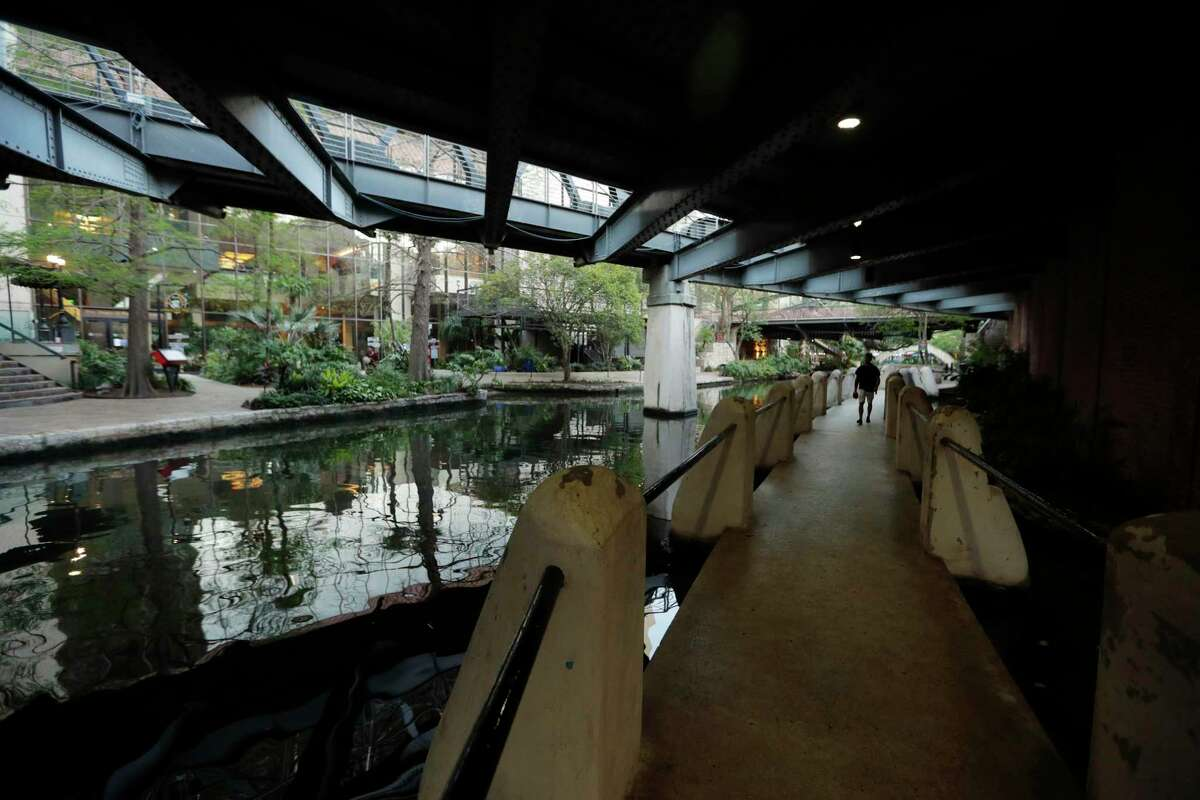 A man walks along a mostly deserted River Walk on Tuesday, March 24, 2020, in San Antonio, where most restaurants and business are closed. San Antonio is joining several other major Texas cities and will begin ordering people to stay at home to battle the spread of COVID-19. (AP Photo/Eric Gay)