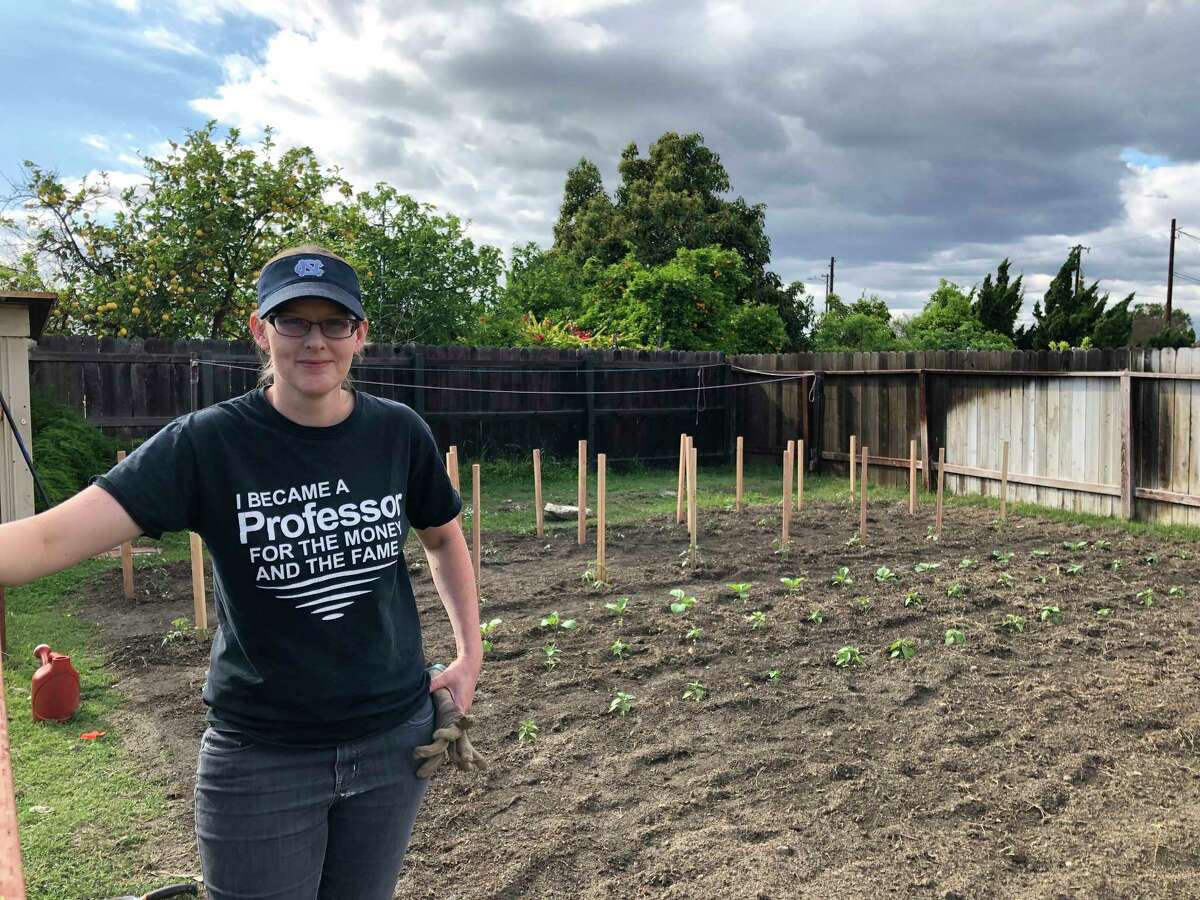 In this March 23, 2020 photo, Lindsay Waldrop stands near her garden at her home in Anaheim, Calif. Waldrop plowed 1,000 square feet of grass to start a garden this year. She has planted dozens of tomatoes, eggplants and peppers with many more crops started as seeds. As the arrival of spring in the Northern Hemisphere coincides with orders to stay at home and out of crowds, the backyard garden has become a getaway for the mind in chaotic times. (Matt Snyder via AP).