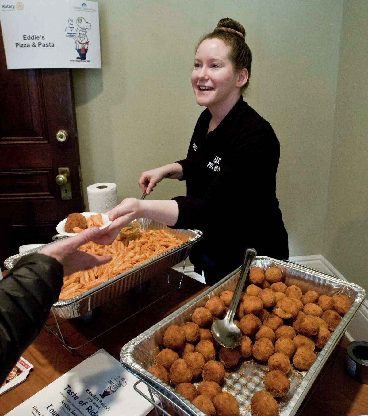 Christa Lowenstein, of Eddie's Pizza & Pasta, serves food during last year's annual Taste of Ridgefield at the Lounsbury House.