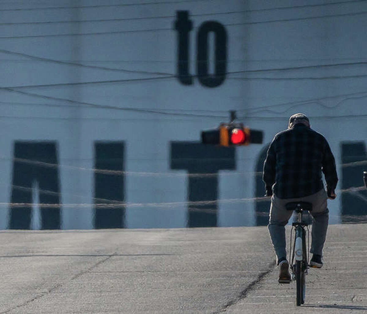 A man makes his way up an empty East Broadway Tuesday afternoon in downtown Alton.