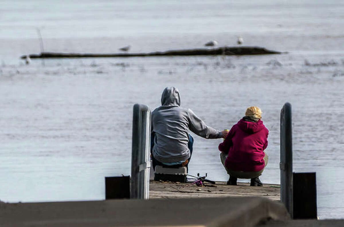 A man and woman share a beverage while fishing under the Clark Bridge on Tuesday.