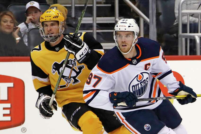 FILE - In this Nov. 2, 2019, file photo, Edmonton Oilers' Connor McDavid (97) and Pittsburgh Penguins' Sidney Crosby (87) skate during the second period of an NHL hockey game in Pittsburgh. Edmonton Oilers captain Connor McDavid is still regarded as the NHLa€™s top forward, while peers consider Pittsburgha€™s Sidney Crosby the game's most complete player, according to the NHL Playersa€™ Associationa€™s annual poll of players released Tuesday, March 31, 2020. (AP Photo/Gene J. Puskar, File)