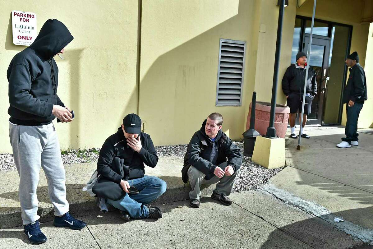 Homeless men, housed at the LaQuinta hotel by the City of New Haven to help stem the tide of the COVID-19 / coronavirus outbreak, congregate together Tuesday, March 31, 2020 near the rear entrance of the Long Wharf Drive hotel in New Haven.