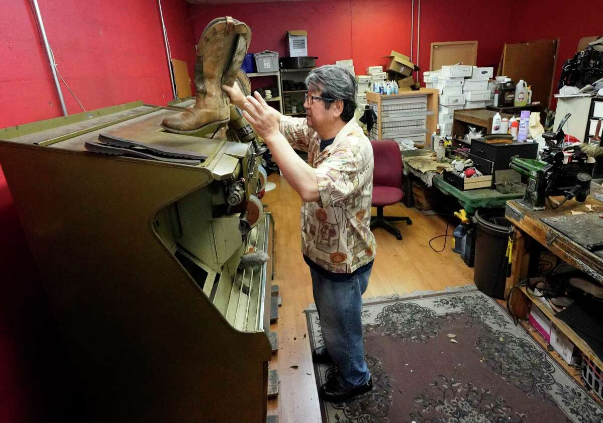Paul Yu, who has been in business over 20 years, works in his shoe repair shop, Tuesday, March 24, 2020, in Tomball, Texas. Yu, who will have to temporarily close his business due to a Stay Home - Work Safe Order, is worried about the loss of income during the closure. A Stay Home - Work Safe Order was issued Tuesday for Houston and Harris County residents to help fight the spread of COVID-19. The order will go into effect at 11:59 p.m. Tuesday night and will last until April 3. Harris County Judge Lina Hidalgo said people should stay home except for essential needs. (AP Photo/David J. Phillip)