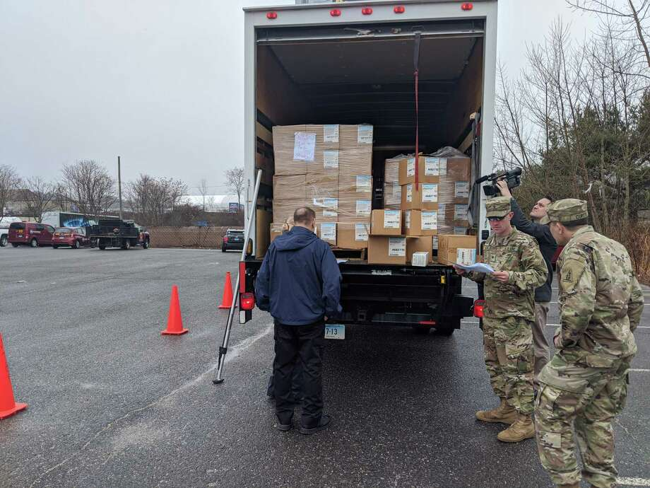 Connecticut National Guard soldiers assigned to the 1048th Transportation Company help state Public Health Department employees distribute protective masks to ambulance companies and other first responders in the state on March 20. Photo: Connecticut National Guard