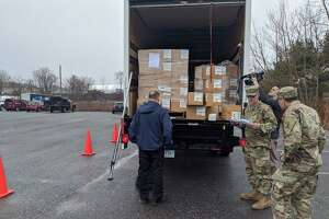 Connecticut National Guard soldiers assigned to the 1048th Transportation Company help state Public Health Department employees distribute protective masks to ambulance companies and other first responders in the state on March 20.