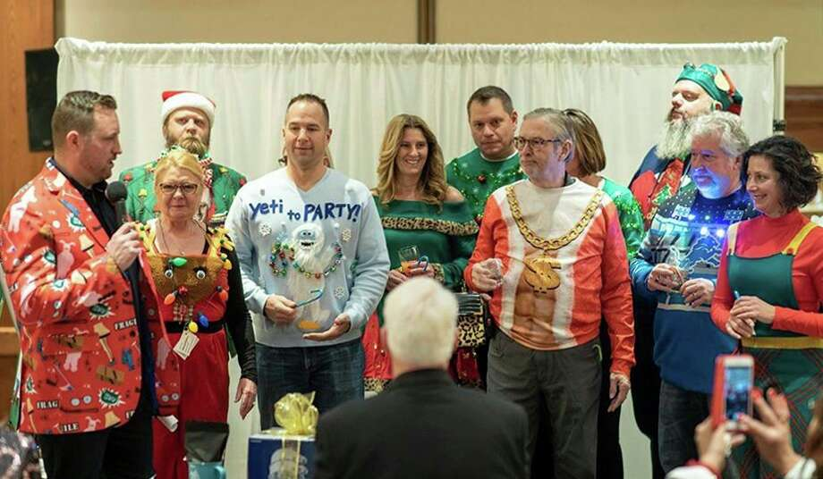 "Peter Baiardi, president of Community Wishes, far left, introduces the ugly sweater contest at last year's Holiday Wishes Gala dressed in a blazer decorated with all things ""A Christmas Story."" Baiardi, Marisa Boulton, Casey Mallek and Wendy Warner formed Community Wishes in 2016. They carry on the Holiday Wishes Gala tradition, a fundraiser that many people have been a part of over the years. Since 2009, the event has raised approximately $280,000 for local non-profits. (Photo by Ben Tierney)"