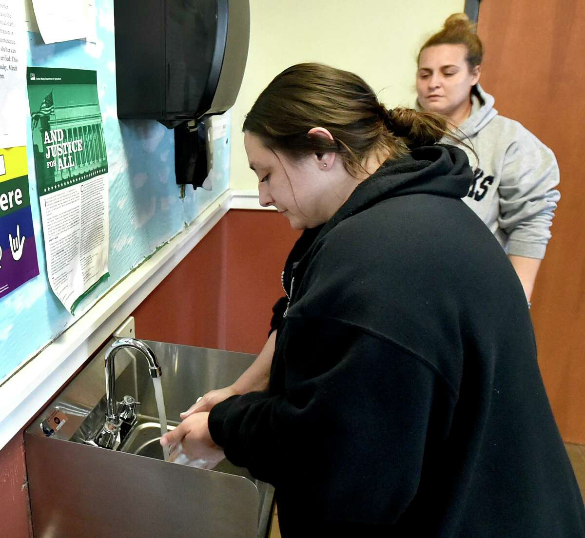 New Haven, Connecticut - Tuesday, March 31, 2020: Jeanna Suraci, 37, left, a resident at the Columbus House homeless shelter in New Haven washes her hands Tuesday in what was a water fountain and just converted into a sink for washing hands as a result of the COVID-19 / Coronavirus pandemic as resident Amber MacDonald (CQ), right, waits her turn. Columbus House is in the process of transitioning the remaining homeless residents there into their own hotel rooms in New Haven in the effort to stem the spread of COVID-19.