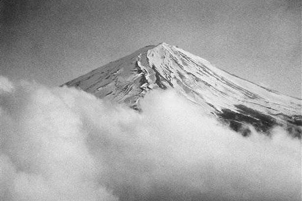 Mist-draped Mt. Fuji, Japans sacred and picture postcard mountain shown April 1, 1949, claimed another American occupation force victim on March 27 when a B-26 light bomber crashed into the peak. The plane, completing a routine training flight, smashed into the rugged reaches at the 9,500 foot level of the 12,467 foot mountain about sixty miles from Tokyo. Sacred Crest, the deceptively smooth top of Mt. Fuji, as seen from the air, are heavily ridged and covered with tough lava. It was over terrain like this that ground searchers of the Third Air Sea Rescue Squadron, based in Japan, toiled to locate wreckage of a B-26 bomber. The crashed plane was the latest of several aircraft, ranging up to heavy transports, which have smashed into the mountain. (AP Photo/Charles P. Gorry)