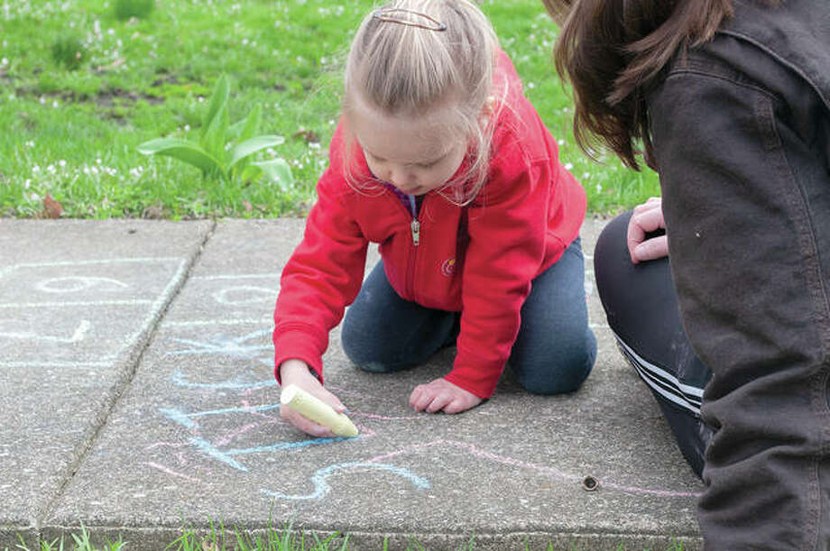 Quincy Musgrove, 3, colors the sidewalk with chalk Tuesday as mom Abby Musgrove watches. They have been practicing social distancing and love to draw on sidewalks, keeping everything as positive as possible.