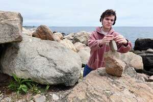 Edmund Rogers of Guilford creates a rock sculpture by balancing rocks on each other amongst the boulders at Hammonasset Point at Hammonasset Beach State Park in Madison on May 29, 2019.